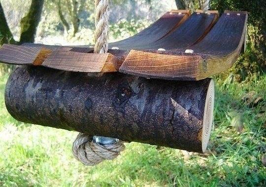 КАК СДЕЛАТЬ САДОВЫЕ КАЧЕЛИ Эти качели ручной работы в деревенском стиле сделаны из ствола упавшего дерева, трех планок от старого винного ящика и крепкой веревки. C помощью длинных гвоздей