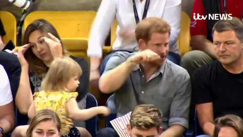 Mother realising her toddler is stealing popcorn from an unaware Prince Harry